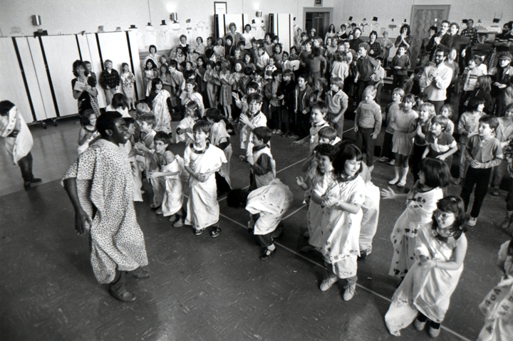 Obo Addy performs in a Portland school with students who have designed their own *adinkra* cloth and are showing the dance steps they have learned, Portland, Oregon, 1988, courtesy Susan Addy
