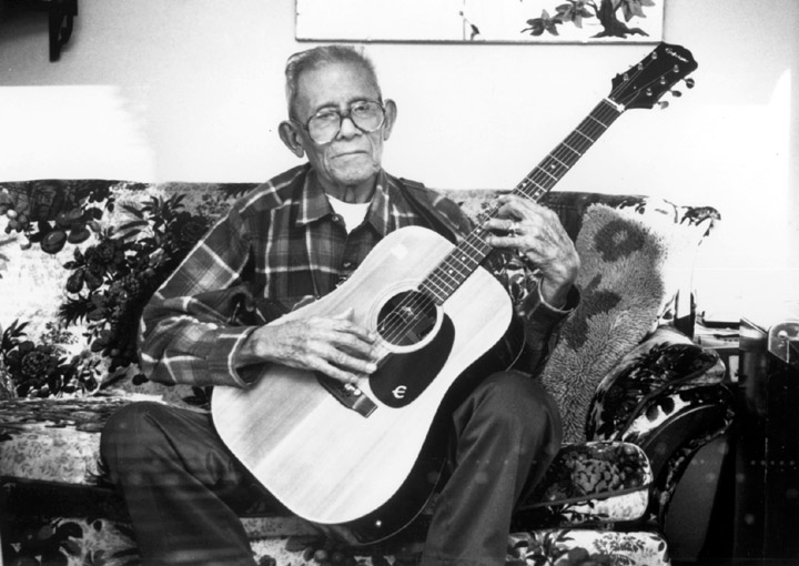 Santiago Almeida's primary instrument was not the standard six-string guitar like the one he is holding here at his home in Sunnyside, Washington. Almeida, a Mexican American from South Texas, helped define the *conjunto* musical style while playing the *bajo sexto*, a twelve-string guitar with bass strings. Photograph by Craig Miller, courtesy National Endowment for the Arts