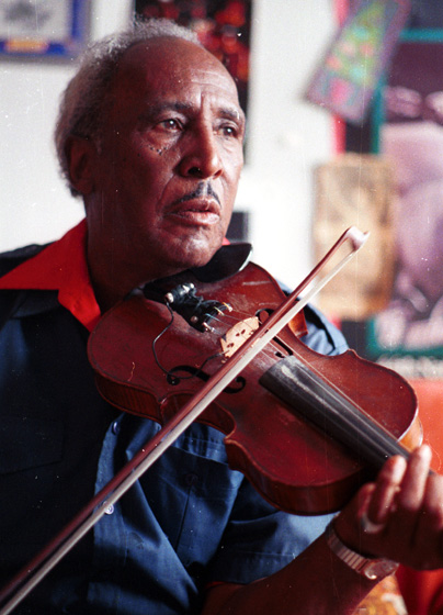 "African American string band musician Howard Armstrong, at his home in Detroit, Michigan, played several instruments but liked the violin best. He called it ""the perfect instrument, the only instrument that all the human emotions can be expressed upon."" 1988, photograph by Laurie Sommers, courtesy Michigan Traditional Arts Program, Michigan State University Museum"