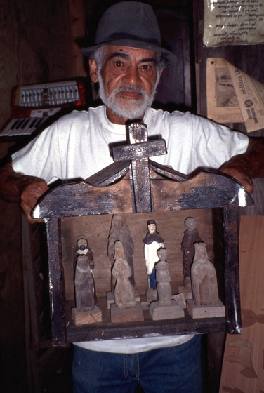 Celestino Avilés carves *santos*, or saints, in a tradition that dates to the Spanish conquest of his native Puerto Rico. Here, he displays his work in his hometown, Orocovis. Avilés works from memory and strives to make each figure from a single piece of cedar. Courtesy National Endowment for the Arts