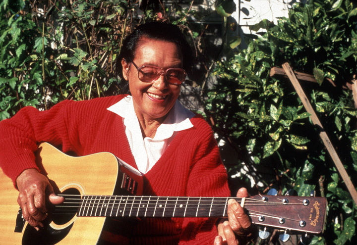 African American guitarist Etta Baker performs outside her home in Morganton, North Carolina. Her Piedmont blues style featured picking with the thumb and two fingers. Photograph by Mary Anne McDonald, courtesy of the North Carolina Arts Council, Folklife Program