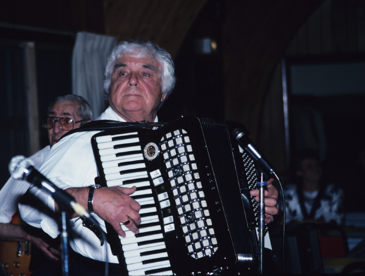 "Slovenian American accordionist Louis Bashell grew up listening to music in his father's Milwaukee tavern. His band played all kinds of music, he said. ""But I try to hang onto the Slovenian heritage because a lot of things are slipping away."" Here he plays for a fiftieth anniversary celebration at a VFW hall in Whitewater, Wisconsin. He also played at the couple's wedding and for their twenty-fifth anniversary. 1991, photograph by Alan Govenar"