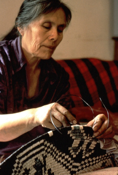 Mary Holiday Black introduced innovations that helped spark a renaissance of Navajo basketweaving. She borrowed ideas from other Native American crafts, using both geometric designs and images with religious significance. Here, she works in her home on the Navajo reservation in Halchita, Utah. 1994, photograph by Carol Edison, courtesy Utah Arts Council