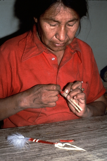 Alice New Holy Blue Legs at work in her home, making dangles by wrapping dyed quills around buckskin strips and hair, Grass Creek, South Dakota, ca. 1980, photograph by H. Jane Nauman, courtesy South Dakota Folk Arts and National Endowment for the Arts