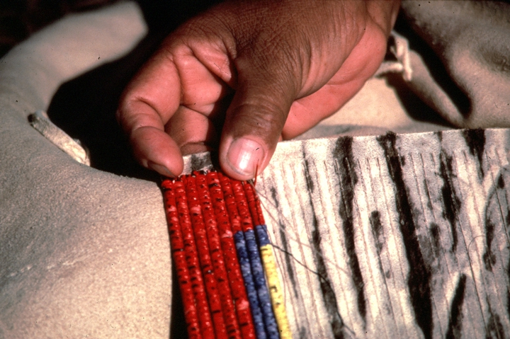 Alice New Holy Blue Legs at work in her home, using sinew to stitch wrapped quills together, Grass Creek, South Dakota, ca. 1980, photograph by H. Jane Nauman, courtesy South Dakota Folk Arts Program and National Endowment for the Arts