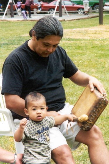 Loren Bommelyn working with his great-nephew Kai Baugh on Kai's first birthday-teaching him how to use a gambling drum, courtesy Loren Bommelyn