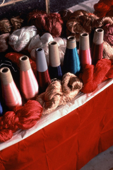 Skeins and cones of silk ready for weaving. A silk tie factory donated remnants of silk for Em Bun's use. Some of the silks Em Bun dyed herself. Harrisburg, Pennsylvania, photograph by Blair Seitz, courtesy National Endowment for the Arts