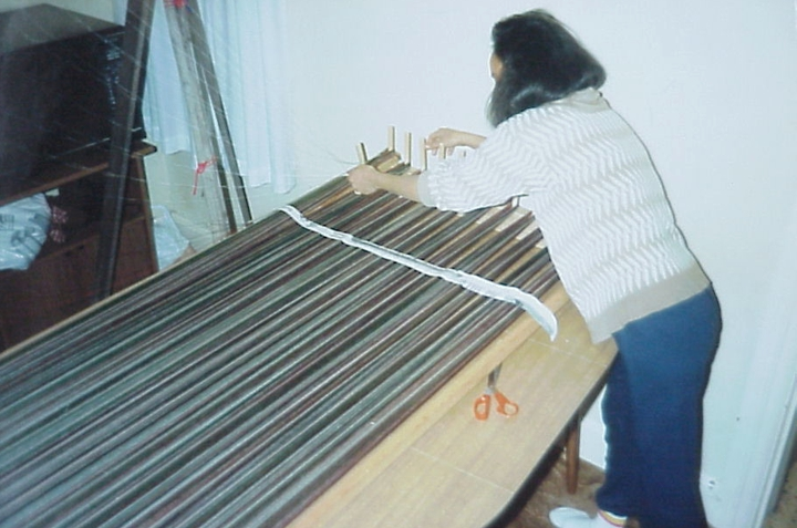 Pech Yuos, daughter of Em Bun, helping at her mother's loom, Harrisburg, Pennsylvania, photograph by Joanna Roe, courtesy National Endowment for the Arts