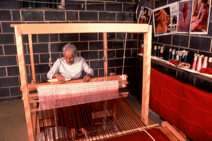 Em Bun at her loom weaving. Her loom is set up in the basement of her home in Harrisburg, Pennsylvania. In Cambodia, looms are traditionally placed under the living quarters and serve as a central gathering place for women and children. The photos on the wall behind Em Bun were given to her by a volunteer who wanted to encourage her to think about weaving silk for the fashion industry. Photograph by Blair Seitz, courtesy National Endowment for the Arts