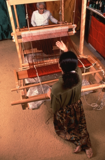 Em Bun's daughter, Pech Yuos, helps her advance the warp on the loom. This loom is 8 feet long and was made by a carpenter in Harrisburg, Pennsylvania from drawings of a traditional Cambodian loom. In Cambodia, this kind of loom is usually twice as long. Photograph by Blair Seitz, courtesy National Endowment for the Arts
