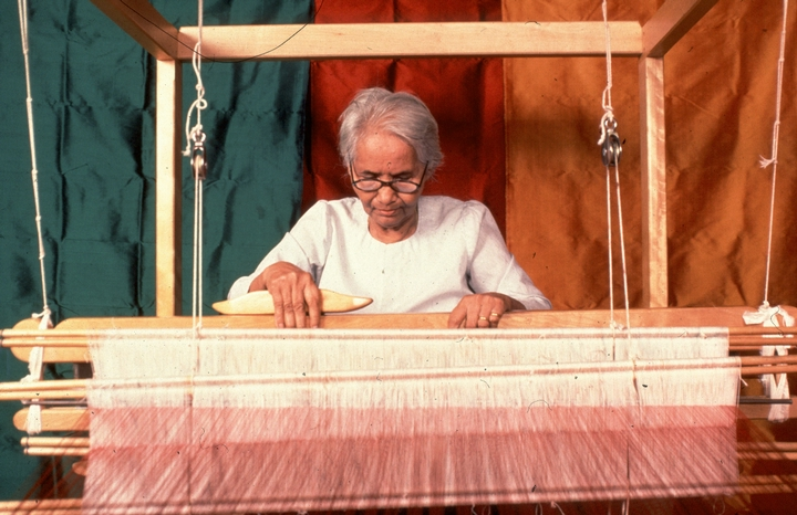 Em Bun weaving. On the walls behind her are samples of her woven fabrics. Harrisburg, Pennsylvania, photograph by Blair Seitz, courtesy National Endowment for the Arts