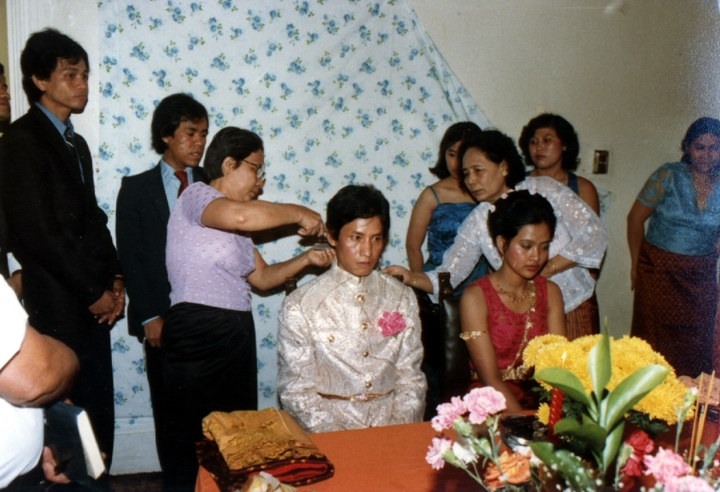 Em Bun's son, Hieng, on his wedding day. An older, close relative cuts a lock of his hair in the traditional Cambodian manner as part of the ceremony. Harrisburg, Pennsylvania, 1985, courtesy Em Bun