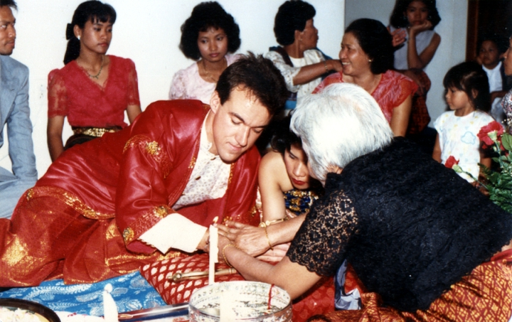 Em Bun ties a thread around the groom's wrist in a traditional Cambodian manner as a blessing on the wedding day of one of her distant relatives. Harrisburg, Pennsylvania, 1987, courtesy Em Bun