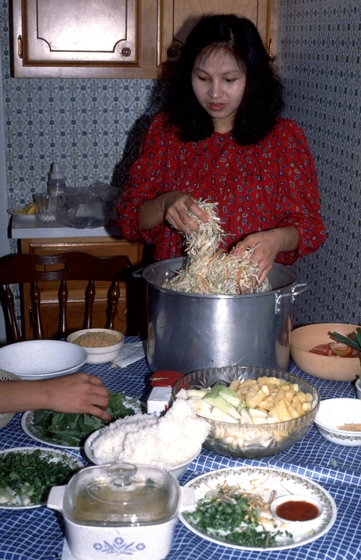 Pech Yuos, daughter of Em Bun, prepares food for a traditional house blessing. Harrisburg, Pennsylvania, photograph by Amy Skillman, courtesy Institute for Cultural Partnerships