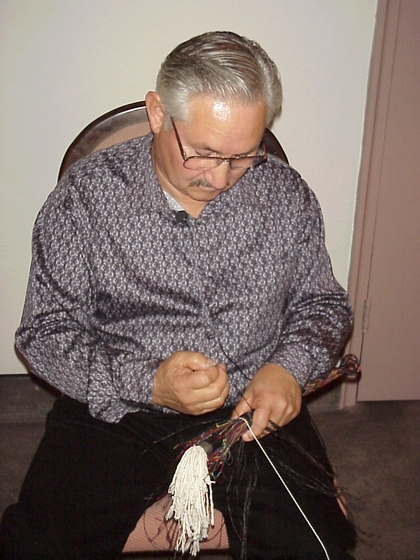 Alfredo Campos at work hitching horsehair to make a quirt (short-handled riding whip), Washington, D.C., 1999, photograph by Alan Govenar