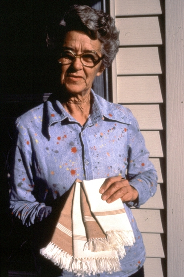 Gladys LeBlanc Clark holding a selection of her woven cotton pieces in front of her home, Duson, Louisiana, photograph by Nicholas R. Spitzer, courtesy Louisiana Folklife Program and National Endowment for the Arts