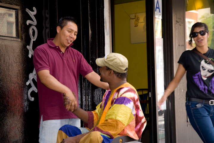 Sidiki Conde greeting friends on First Avenue near his apartment, New York City, 2011, photograph by Alan Govenar