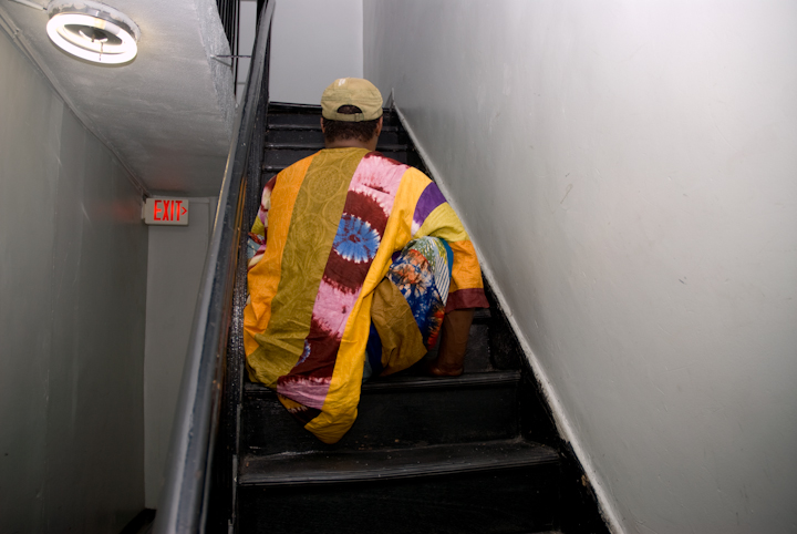 Sidiki Conde climbs the stairs to his fifth-floor apartment on his hands, New York City, 2011, photograph by Alan Govenar