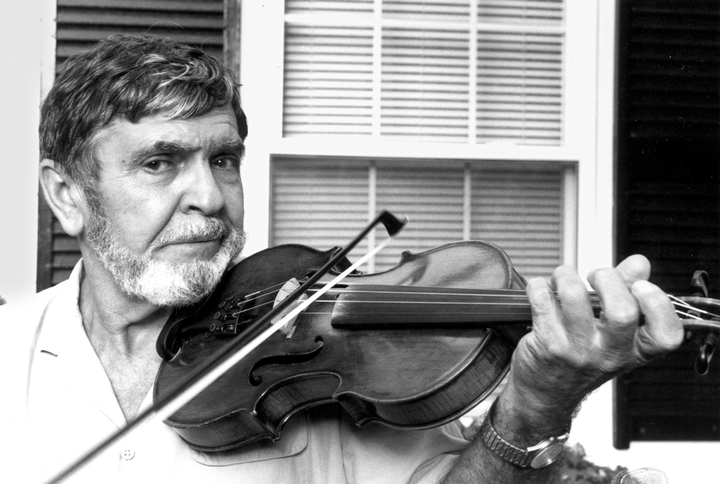Joseph Cormier demonstrates his fiddling in front of his home in Waltham, 1990, photograph by Alan Govenar