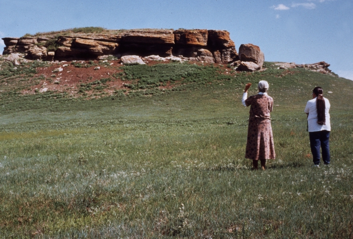 'Mary Louise Defender-Wilson is shown here offering a prayer in order to tell the story about this butte on the Cheyenne River Indian Reservation. She is teaching the story to Dakotah language speaker Thomasine Loans Arrow from Cannonball (on the Standing Rock Reservation in North Dakota). Mary Louise and Thomasine received a North Dakota Council on the Arts Traditional Arts Apprenticeship Program grant in 1998 to teach/learn traditional stories.' June 15, 1998, comments and photograph by Troyd Geist, courtesy North Dakota Council on the Arts