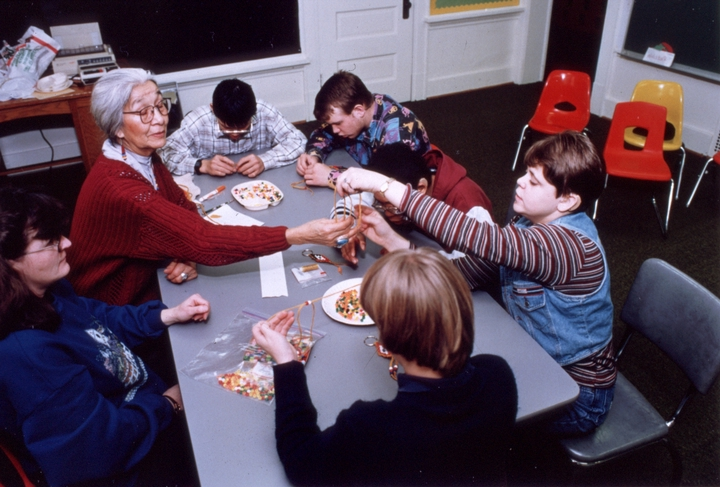 """Mary Louise Defender-Wilson often gives storytelling presentations to children in and out of schools. Sometimes they are formally sponsored, sometimes she volunteers. She is shown here working with children at the North Dakota School for the Deaf in Devils Lake, North Dakota."" November 18, 1998, comments and photograph by Troyd Geist, courtesy North Dakota Council on the Arts"