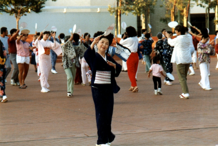 Madam  Fujima has remained active in the annual Nisei Week Japanese Festival in the Los Angeles community, where she served in 1986 as the official choreographer. Here, she teaches the public her dance movements in preparation for the parade. She reprised that role in 2010, at age 92. Courtesy Fujima Kansuma Kai of Los Angeles