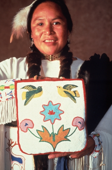 Sophia George holding a beaded bag with her flower design, courtesy National Endowment for the Arts