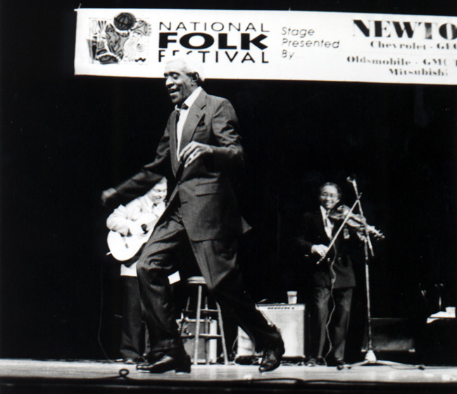 "African American tap dancer James ""Jimmy Slyde"" Godbolt, who once worked with the great big bands of the 1940s, performs his signature steps on stage at the National Folk Festival. Photograph by Joseph T. Wilson, courtesy National Council for the Traditional Arts"