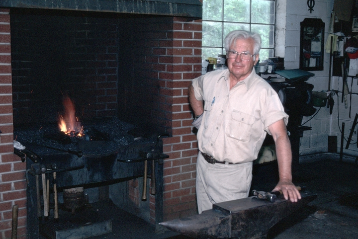Bea Ellis Hensley developed a full range of blacksmithing skills while working as an apprentice to Daniel Boone VI, a descendant of the famous frontiersman. Like his teacher, Hensley excelled at both utilitarian and ornamental ironwork, usually combining the two in projects such as knives, andirons, fire sets and gates. Spruce Pine, North Carolina, 1997, photograph by Alan Govenar