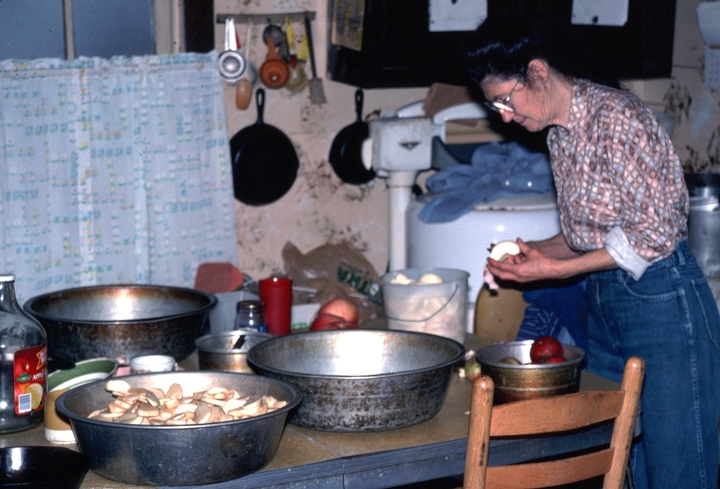 Ray Hicks' wife, Rosa, slicing and drying apples in the kitchen of their cabin, Banner Elk, North Carolina, 1991, photograph by Alan Govenar