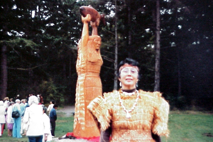Violet Hilbert wears a cedar bark dress, the traditional clothing of the Northwest Coast Indian people. It is woven from the soft inner bark of the cedar tree. This dress was made by one of her elders and was used as a model for the dress in the carving in the pole behind her. September 1983, courtesy National Endowment for the Arts