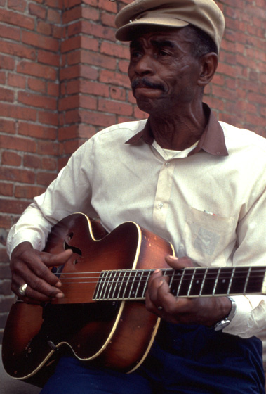 "John Dee Holeman of North Carolina is a Piedmont blues guitarist and singer who also embraced the tradition of ""patting juba,"" using complex hand rhythms to accompany himself and others as he danced. 1993, photograph by C.N. Chatterley, courtesy North Carolina Arts Council, Folklife Program"