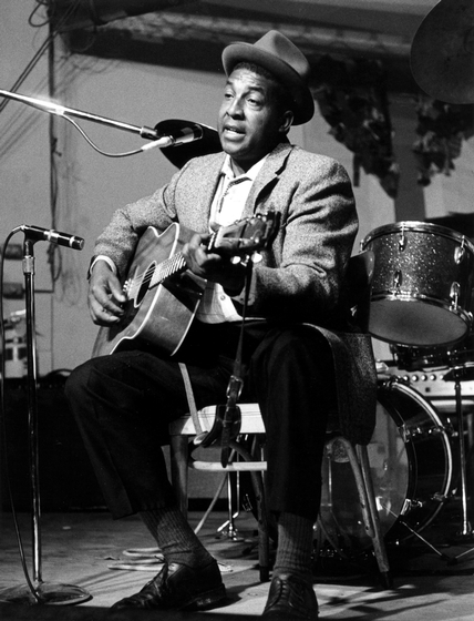 Piedmont blues guitarist John Jackson grew up in rural Virginia. He was influenced early on by the music he heard on record: blues, hillbilly, gospel, ragtime and country hymns. He was one of the few contemporary African Americans to also play blues on the banjo. European Tour, 1970, photograph by Chris Strachwitz/Arhoolie Records