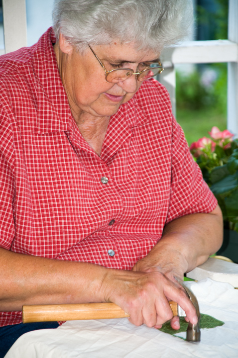 Bettye Kimbrell pounding a kudzu leaf to extract the dye from the kudzu leaves. This technique, Bettye says, is called 'Cherokee leaf pounding,' Mt. Olive, Alabama, 2008, photograph by Alan Govenar