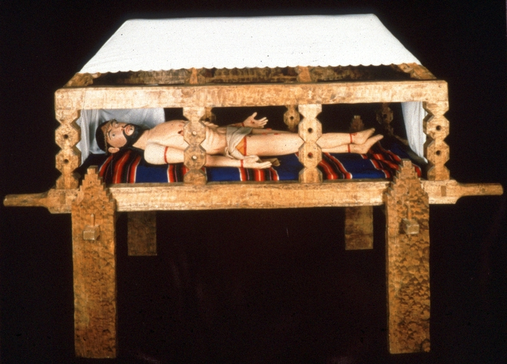 "'Santo Entierro' (The Entombed Christ) by Ramón José López, hand-adzed and carved aspen, gesso, egg tempera and buckskin arms and head of Christo articulated; head on center pivot sepulcher is tendon and mortise, dovetail joints. 1985, courtesy National Endowment for the Arts. Christo: life-size,  8"" diameter at head, 6' tall. Sepulcher: 3' x 8' x 3.' Sepulcher stand: 3' x 8' x 3 1/2'"