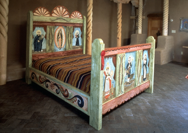 'Cama de Suenos' (Bed of Dreams) by Ramón José López, large, hand-carved, painted with natural pigments and vegetable dyes. Queen-size bed with six images of *santos* painted on hand-carved foot and head board. Buffalo rawhide box spring with two hand-made mattresses of muslin stuffed with the wool from eighteen buffalos. Courtesy National Endowment for the Arts