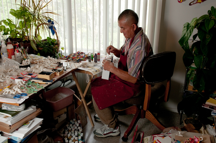 Jeronimo E. Lozano painting a *retablo* figure in his apartment, Salt Lake City, Utah, 2009, photograph by Alan Govenar