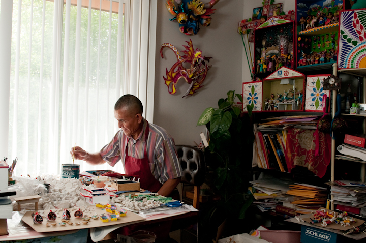 Jeronimo E. Lozano painting *retablo* figures in his apartment, Salt Lake City, Utah, 2009, photograph by Alan Govenar