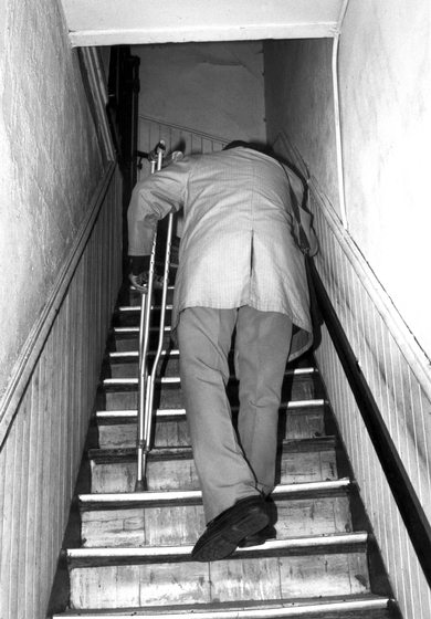 Albert 'Sunnyland Slim' Luandrew at age 84 going upstairs to his apartment, Chicago, Illinois, 1991, photograph by Alan Govenar