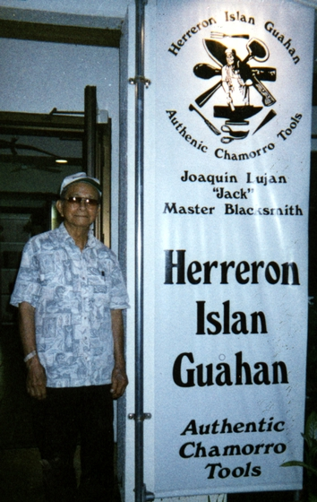 Joaquin Lujan with a banner in front of his shop. Courtesy Joaquin Lujan