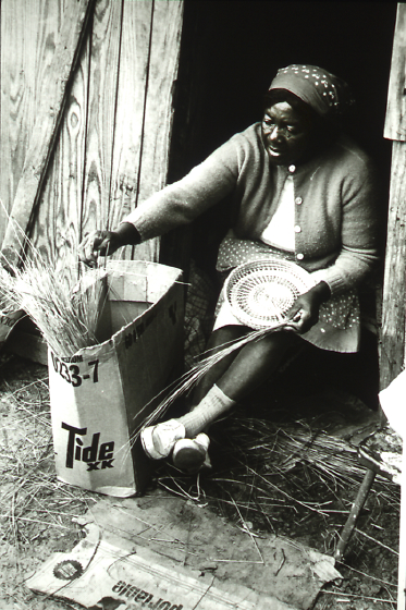 Mary Jane Manigault of Mount Pleasant, South Carolina, crafted her baskets by twining narrow palmetto strips around bundles of sweetgrass and pine needles. She liked to demonstrate her technique as she sold baskets in Charleston's open-air Market Square. Circa 1971, photograph by Dale Rosengarten, courtesy Folklife Resource Center, McKissick Museum, University of South Carolina, Columbia, South Carolina