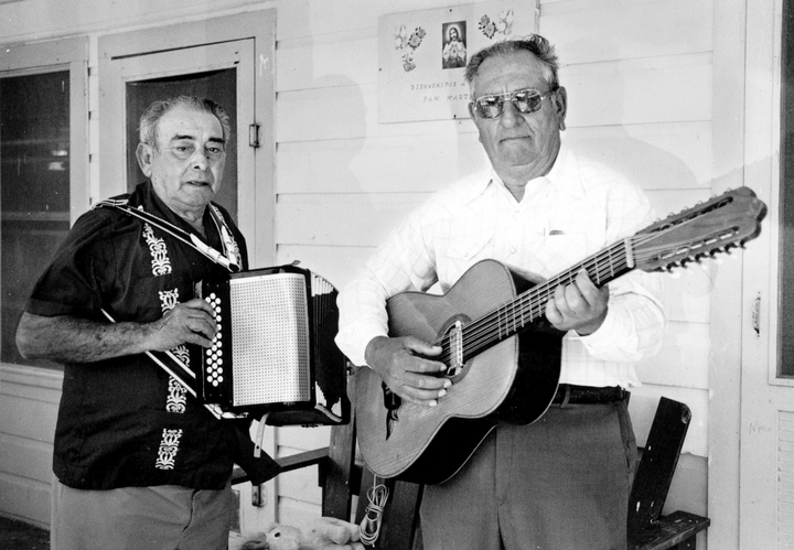 Narciso Martínez (left) was an innovator in the development of what is now called *conjunto* music. Playing the diatonic button accordion, Martínez focused on right-hand virtuosity, leaving the rhythm to instruments such as the *bajo sexto*, played here by Antonio Ramirez in San Benito, Texas. 1986. Photograph by Alan Govenar