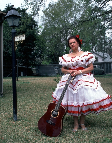 "Lydia Mendoza used her voice and guitar to express a passion for music dating back to her childhood. With the success of her first solo recording in 1934, she became known as ""the Meadowlark of the Border."" She is pictured here in front of her home, Houston, Texas, 1991, photograph by Alan Govenar"
