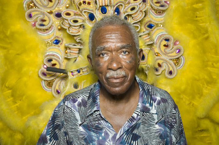 Allison 'Tootie' Montana was Big Chief of the Yellow Pocahontas tribe of New Orleans' Black Mardi Gras Indians for many years. He has worked as an innovative costume designer, a brilliant dancer, and an eloquent spokesman for African American people of Creole descent. Pictured here in front of one of his Mardi Indian suits, New Orleans, Louisiana, 2004, Photograph by Alan Govenar
