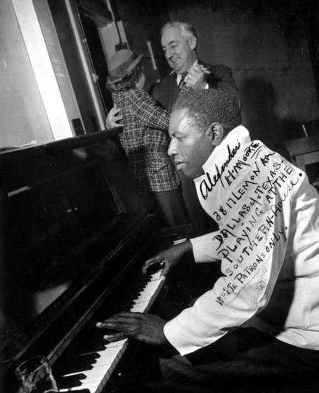 "Alexander H. Moore playing at the Southern House,  Dallas, Texas, in 1947, still wearing his dishwasher coat. His inscription reads in part  ""White Patrons Only."" Courtesy Documentary Arts"