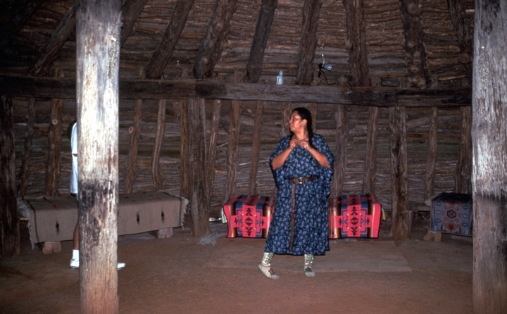 Vanessa Paukeigope Morgan (now Jennings) standing in her earth lodge, Fort Cobb, Oklahoma, 1994, Photograph by Georgetta Stonefish, Courtesy Fred Nahwooksy