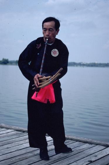 Bua Xou Mua playing the *gaeng* (reed mouth organ), Dallas, Texas, 1991, photograph by Alan Govenar