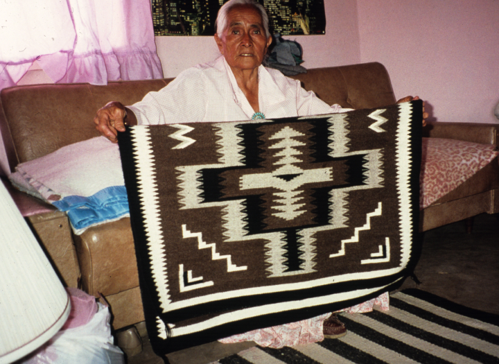 "Navajo weaver Grace Henderson Nez created rugs and blankets with complex, balanced designs, always featuring the correct wool quality, yarn weight and weaving texture. ""That's what gave me life,"" she said of weaving. Here, she shows one of her hand-woven rugs, Photograph by GFR, courtesy National Endowment for the Arts"