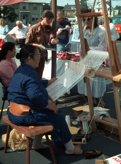 Yang Fang Nhu works at her loom, Smith Hill Neighborhood Festival, Providence, Rhode Island, photograph by Winifred Lambrecht, courtesy Rhode Island State Council on the Arts