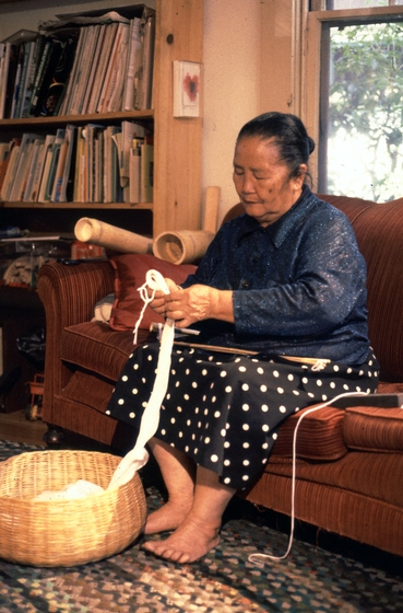 Yang Fang Nhu puts sticks through the eye at the end of her warp. Providence Rhode Island, August 1985, photograph by Winifred Lambrecht, courtesy Rhode Island State Council on the Arts